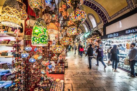 Nicht identifizierte Leute, die den großartigen Basar für den Einkauf, besichtigen. Innenraum des großartigen Basars mit den mehrfarbigen türkischen Lampen des traditionellen handgemachten dekorativen Mosaiks für den Verkauf, der an der Vorderseite hängt. Istanbul, Turkey.April 17, 2017 Editorial