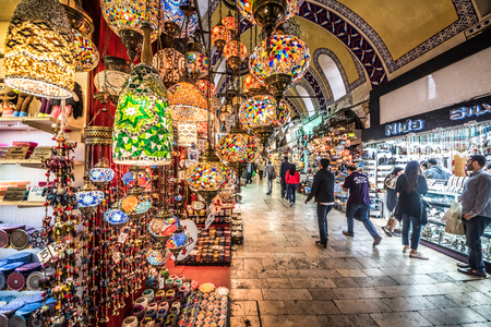 Unidentified people visiting the Grand Bazaar for shopping,.Interior of the Grand Bazaar with traditional handmade decorative mosaic multi-colored Turkish lamps for sale hanging on the front side.Istanbul, Turkey.April 17, 2017