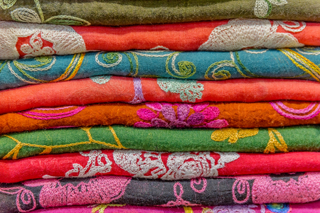 Traditional colorful silk ,cashmere head scarves or shawls and fabrics composed of a stack background at the bazaar stall in Istanbul, Turkey Stock Photo
