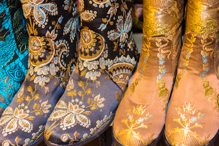 Market stall with pairs of colorful Asian style boots on stall top view in Grand Bazaar Turkey