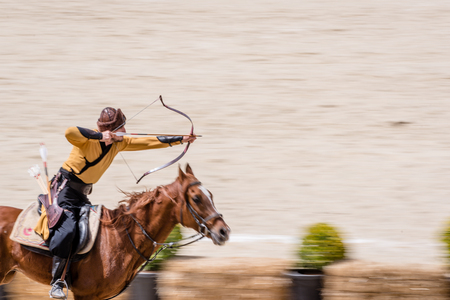 Unidentified people in costumes of ancient Ottoman Empire archer soldiers shoots at archery competition while riding horse.ISTANBUL,TURKEY,May 13,2017