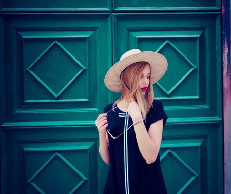 Jonge aantrekkelijke vrouw in modieuze zwarte jurk en stijlvolle ronde zonnebril en gele hoed vormt voor muur op straat. Retro en vintage filter en kleuren effect gebruikt.