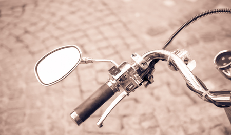 Close up of classic motorcycle shinny handlebar and chrome motorcycle speedometer on a street.