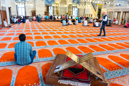 Unidentified Turkish Muslim men praying in Suleymaniye mosque.Old ancient Rahle (lectern) furniture is on foreground.Istanbul,Turkey.04 June 2017