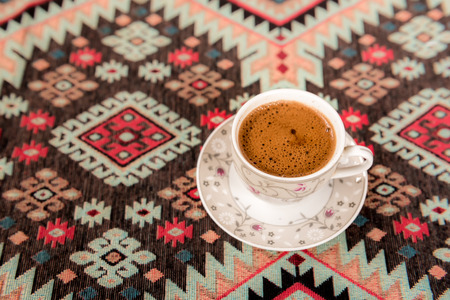 Top view of Traditional Turkish coffee cooked on embers is served in a cup on a traditional Turkish rug.