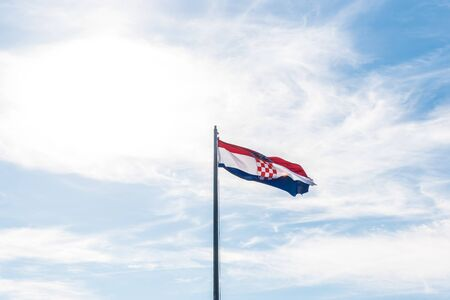 Flag of Croatia waving in the wind with highly detailed fabric light blue sky on the background and space for editing