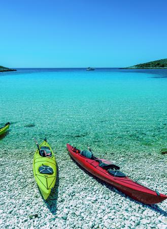 Yellow and red sea canoes on beach with blue sky and sea background on a bay of  Kornati islands, National park in Croatia, Adriatic sea, in Sibenik,Croatia