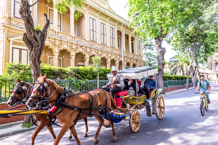 """Coach or Horse carriage with tourists at Buyukada (meaning """"Big Island"""" in English) or Prince Island.Buyuk ada is famous for beautiful streets and phaeton tour in Istanbul,Turkey.20 May 2017"""