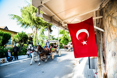 Coach or Horse carriage with tourists at Buyukada (meaning Big Island in English) or Prince Island.Buyuk ada is famous for beautiful streets and phaeton tour in Istanbul,Turkey.20 May 2017
