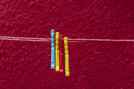 Vintage view of colorful Clothes pegs pinned to a bench with red wall in a background hanging on a clothes rack Banque d'images