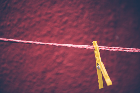 Vintage view of yellow Clothes pegs pinned to a bench with dark red wall in a background hanging on a clothes rack