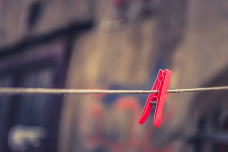Vintage view of colorful Clothes pegs pinned to a bench with on building at background hanging on a clothes rack  Stock Photo
