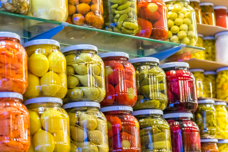 Store shelves with Various pickles in glass jar display for sale Фото со стока
