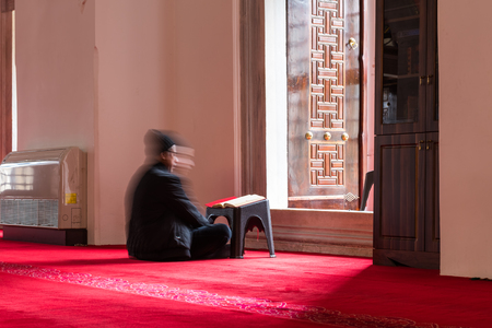 Slow Shutter Speed:Unidentified Muslim man reads Quran at Valide-i Cedid Mosque located in Uskudar,Istanbul,Turkey.03 January 2018 Editorial