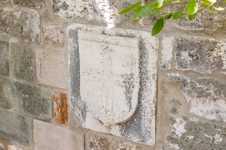 Cross and other signs carved into the wall of ancient Roman marble sculpture in Castle of St. Peter or Bodrum Castle, Turkey.