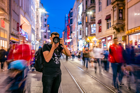 Long exposure or slow shutter speed and blurred image:Unidentified man takes picture at Istiklal street,popular destination in Istanbul,Turkey.29 April 2018 Redactioneel