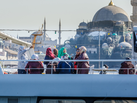 Unidentified people enjoy on ferry with new mosque view on background in Istanbul,Turkey.29 April 2018