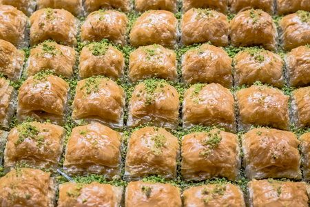 Top Close detailed view of traditional delicious Turkish dessert named baklava with grinded pistachio over.