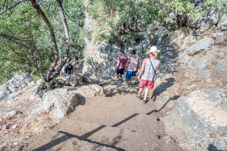 Unidentified people going down to stone slippery stairs towards cave of Chasm of Heaven in Silifke district, Mersin Turkey.29 August 2017.
