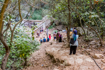 Unidentified people going down to stone stairs towards cave of Chasm of Heaven in Silifke district.Virgin Mary Church built by St. Paulus is in the background.Mersin Turkey.29 August 2017. Editorial