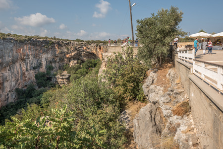 Unidentified people looking at Chasm of Heaven located in Silifke district, Mersin Turkey.29 August 2017. Редакционное