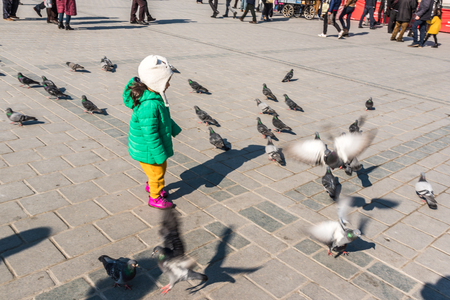 ISTANBUL/TURKEY- DECEMBER 24,2016: Unidentified children feed pigeons in The New Mosque (Yeni Camii). The New Mosque is an Ottoman imperial mosque completed in 1665, located in Istanbul, Turkey.
