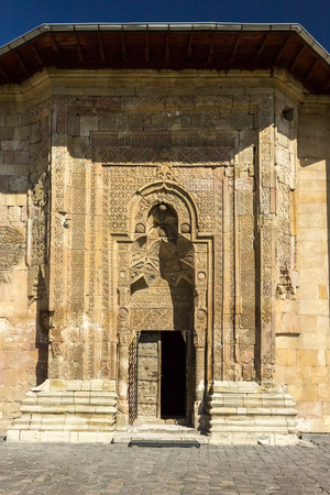 Exterior view of Sivas Divrigi Great Mosque and Praying man silhouette on gate