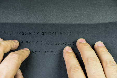 Top view of hand of a blind person reading a book written in braille alphabet for blind people.Copy space for editing. Foto de archivo