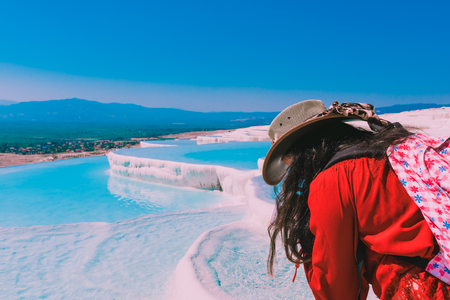 Unidentified woman watch Pamukkale (Cotton Castle) that is popular with Travertine pools and terraces where people love to visit in Pamukkale, Turkey.