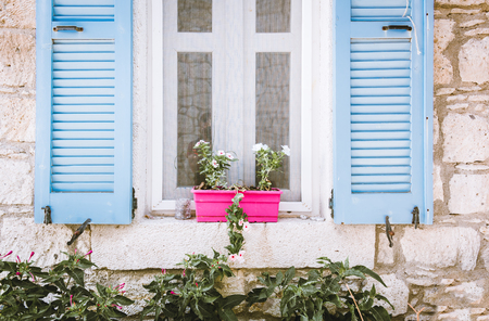 View of a Turquoise color opened wooden window with pink flowerpots above and green plants under window.Ancient white stone wall on the background. Foto de archivo