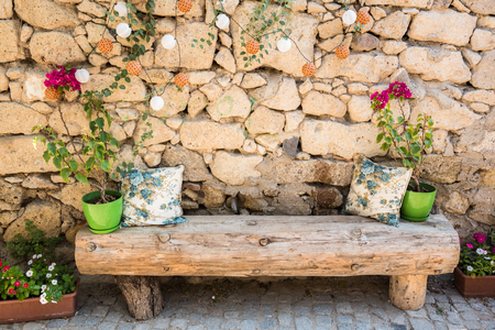 Street view of old wooden chair ,green flowerpots and pillow above it with hanging decorative lamps on ancient white stone wall.