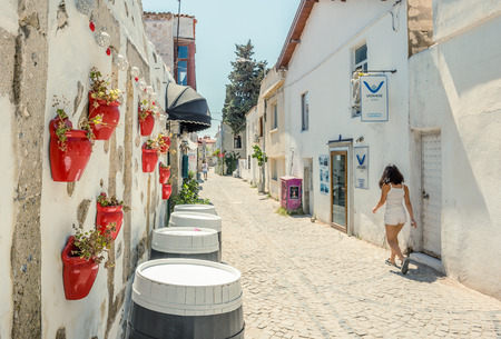 Unidentified People walk at a street with cafe and restaurant with tables and chairs  around at Alacati Town,a popular destination for traveling and vacation in Izmir,Turkey.26 August 2017.Retro Photo Filter Effect Editorial