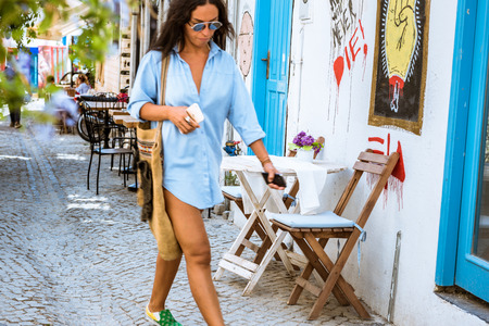 Unidentified woman walking at Alacati charming Streets , a popular destination for traveling and vacation in Izmir,Turkey.26 August 2017.