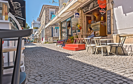 HDR Image-View of cafe and restaurant with tables and chairs at Alacati narrow stone Streets,a popular destination for traveling and vacation in Izmir,Turkey.