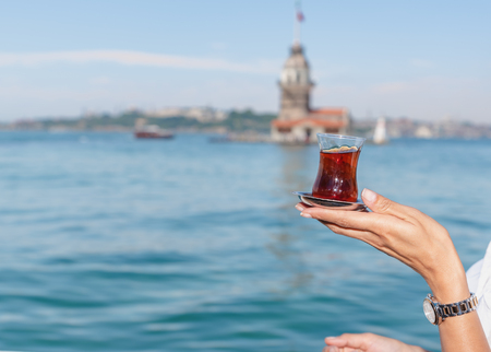 Beautiful woman traveler holds traditional Turkish tea glass in background of Maiden Tower,a popular destination in Istanbul,Turkey