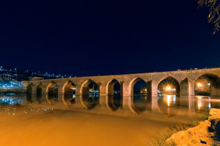Night view of ancient stone ten eyed bridge,a popular landmark in central of Diyarbakir,Turkey. Stock Photo
