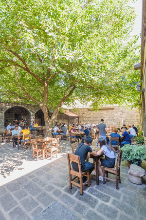 Unidentified people sit courtyard of Suluklu Khan,a medieval inn used for cafes and small shops now in Diyarbakir,Turkey.16 July 2018