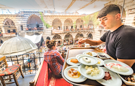 Unidentified man serves for breakfast at Hasan Pasha Khan,a medieval inn used for cafes and small shops now in Diyarbakir,Turkey.16 July 2018