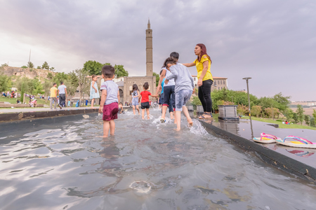 Unidentified children have fun in fountain pool at public park with view of Hazreti Suleyman Mosque on background in sur region,Diyarbakir,Turkey.15 July 2018 Editöryel