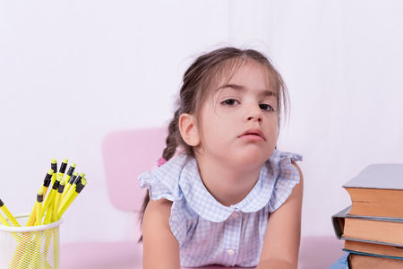 Cute little girl in school uniform looks thoughtful at table.Selective focus and copy space for editing 版權商用圖片