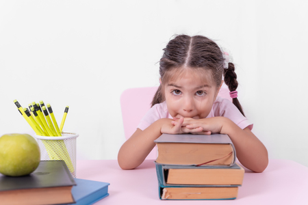 Cute little girl in school uniform looks thoughtful on books.Selective focus and copy space for editing 写真素材