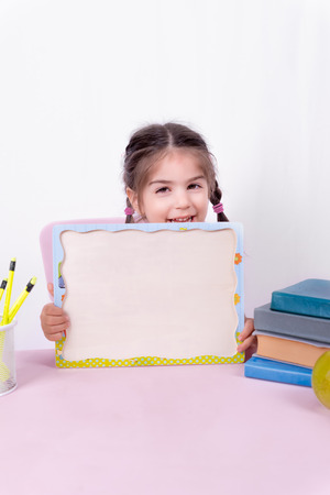 Cute little girl in school uniform holds blank white board.Selective focus and copy space for editing Foto de archivo