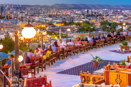 Unidentified sit a terrace cafe over Golbasi Park to watch sunset Sanliurfa,Turkey.18 July 2018