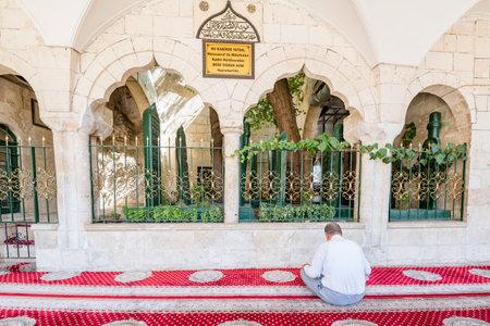 Unidentified man prays at Sheikh Osman Avni tomb, mausoleum at courtyard of Mevlidi Halil Mosque in Sanliurfa,Turkey.19 July 2018