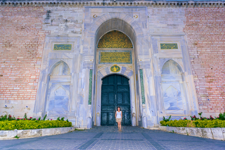 Beautiful woman poses with view of Topkapi Palace on background in Istanbul,Turkey