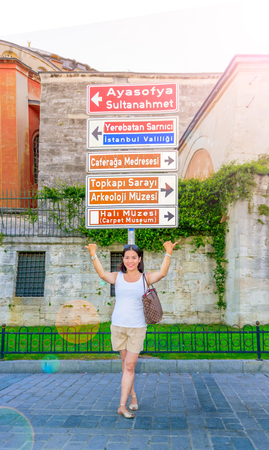 Beautiful woman poses in front of signboard showing popular landmarks of Istanbul,Turkey
