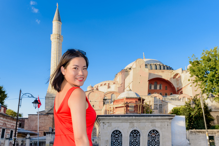 Beautiful woman poses with view of Hagia Sophia on background in Istanbul,Turkey