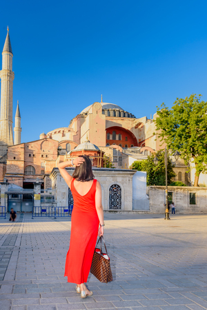 Beautiful woman poses with view of Hagia Sophia on background in Istanbul,Turkey Stock Photo - 114047829