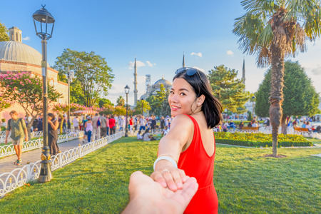 Beautiful woman poses with view of Sultanahmet or Blue Mosque on background in Istanbul,Turkey.Follow me concept Archivio Fotografico
