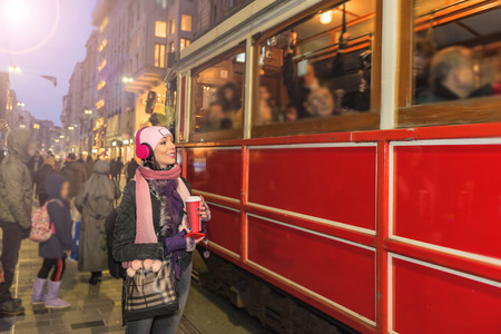 Beautiful woman in beanie with takeaway coffee and headphones poses in front of nostalgic tramway at istiklal street,Istanbul,Turkey